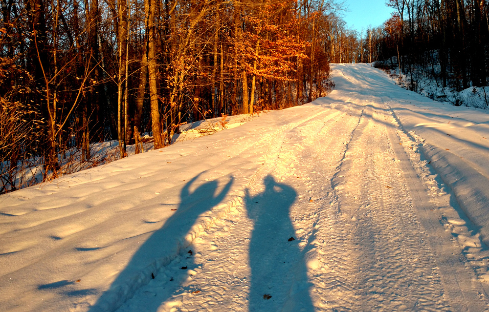 Photo of Mama and Papa in silhouette on the snow-covered road leading down from the look-out tower at Parc Mont-Morisette