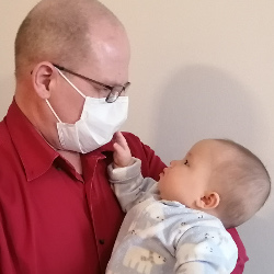 Baby touches her masked father