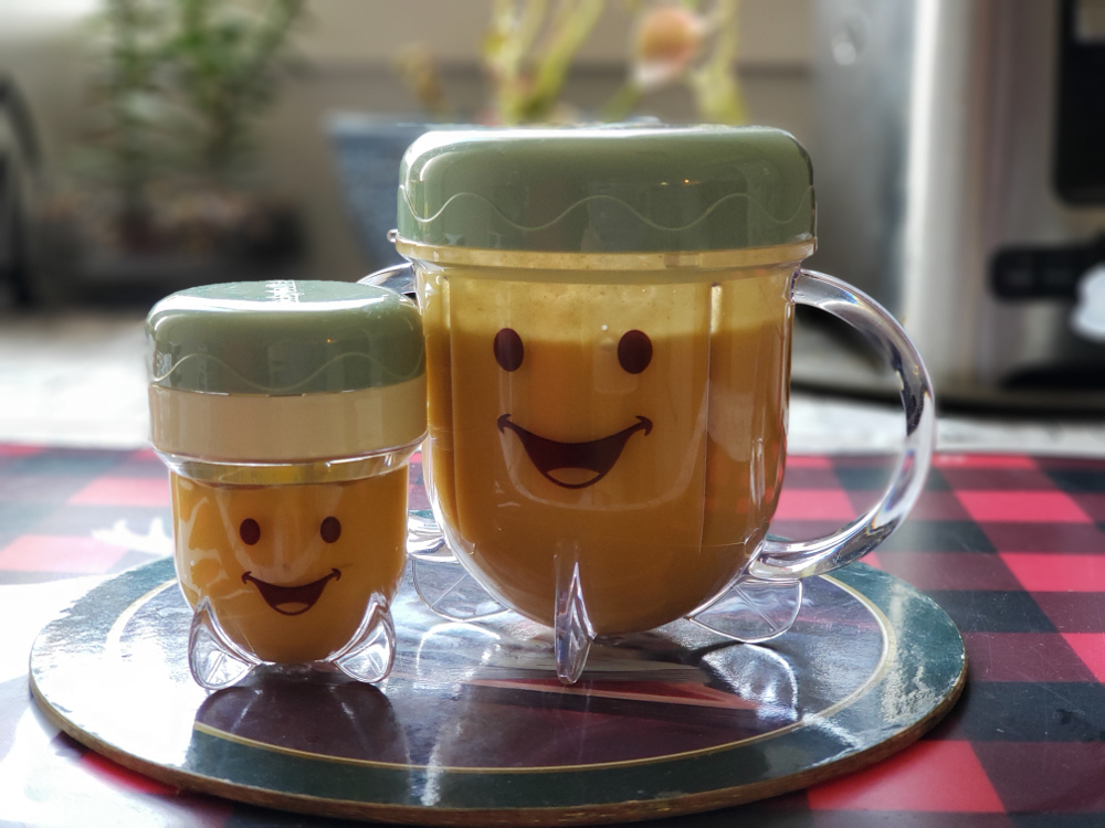 Photo of small and large plastic jars with smiley faces of home-made baby-food.