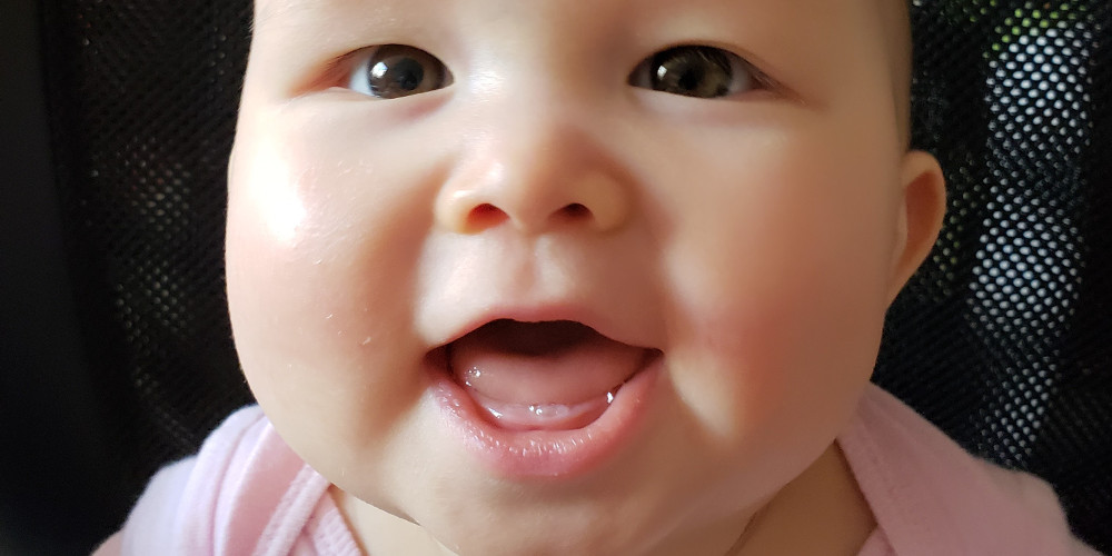 close of photo of smiling baby showing her first tooth.