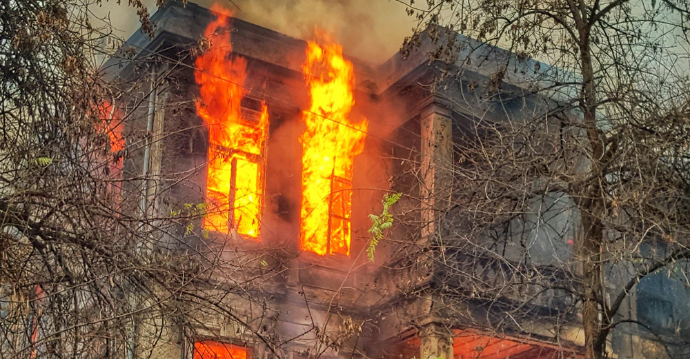 Detail of photo of building in flames by Chris Karidis via Unsplash.
