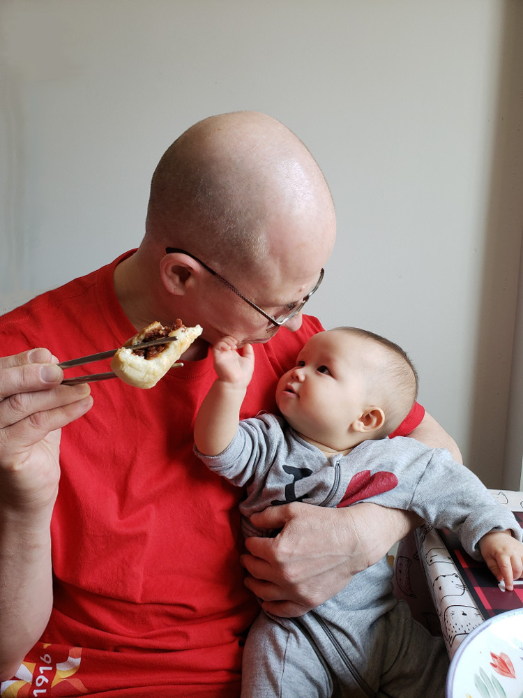 Photo of Papa Zesser holding a partially-eaten bar-b-q pork bun in chopsticks, while holding Baobao in his left arm as she reaches for his chin.