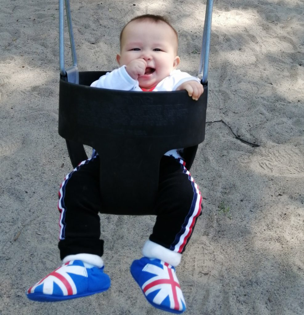 Detail of photo of baby Baobao on a swing for the very first time.