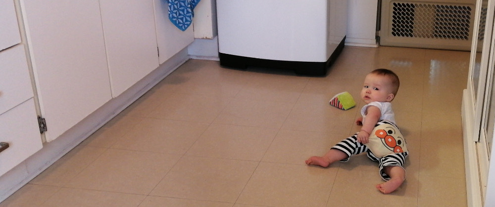 Photo of Baby Baobao crawling on the kitchen floor.