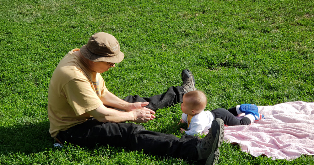 Photo of baby Baobao with Papa Zesser on the grass in a park.