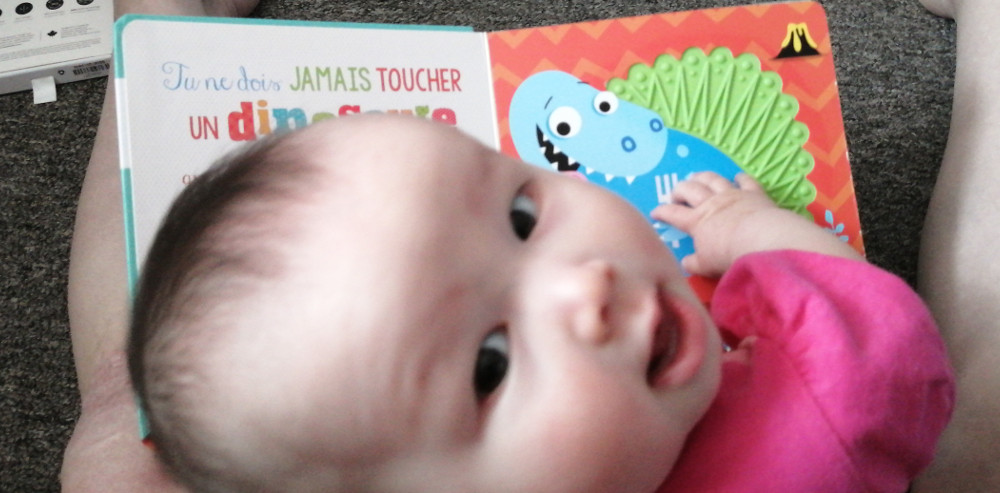 Photo of baby Baobao with the book, Ne touche jamais un dinosaure!