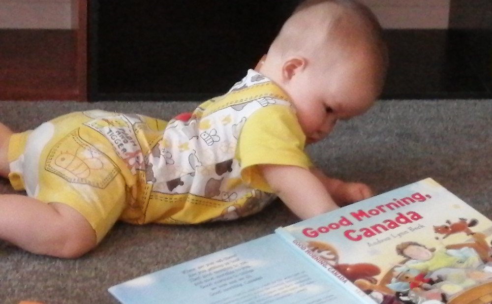 Baby Baobao examines the book, Good Morning, Canada, while crawling on floor