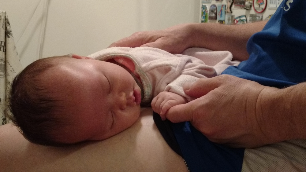 Photo of Baby Baobao sleeping on Papa Zesser lap while holing his left index finger.