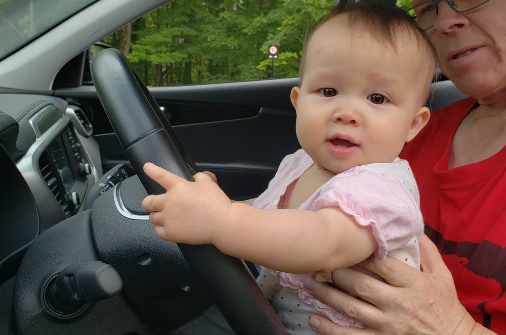 Photo of baby Baobao on Papa Zesser's lap holding the steering wheel of an SUV.