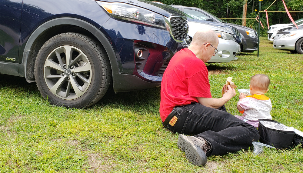 Detail of photo of Papa Zesser helping Baobao eat in front of their rental car.