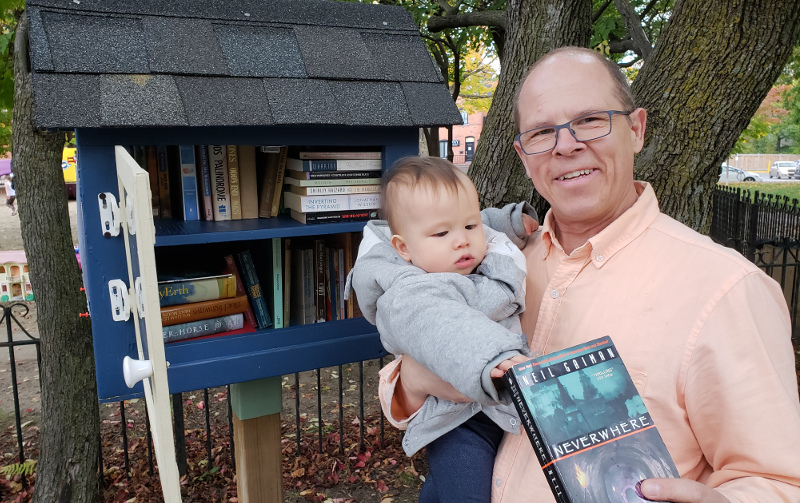 Photo of Papa Zesser holding baby Baobao in front of local little library, about to return Neil Gaiman's not-so-good book, Neverwhere.