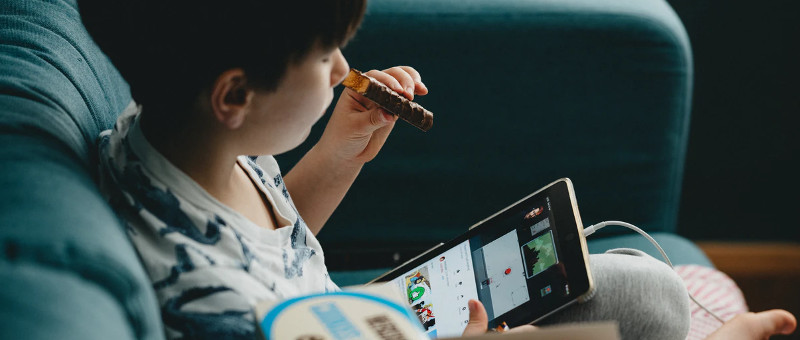 Detail of a photo of a child seated on a chair or couch, holding a tablet in one hand and a half-eaten chocolate bar in the other. Image via Unsplash.com by @anniespratt.