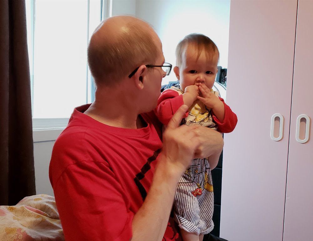 Photo of Papa Zesser holding toddler Baobao while explaining something to her. Photo by Mama Raven, November 11, 2020.