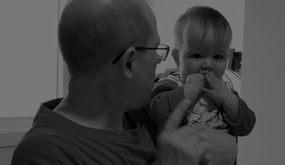 Black and white photo of Papa Zesser wagging his finger at toddler Baobao. Photo by Mama Raven, November 11, 2020.