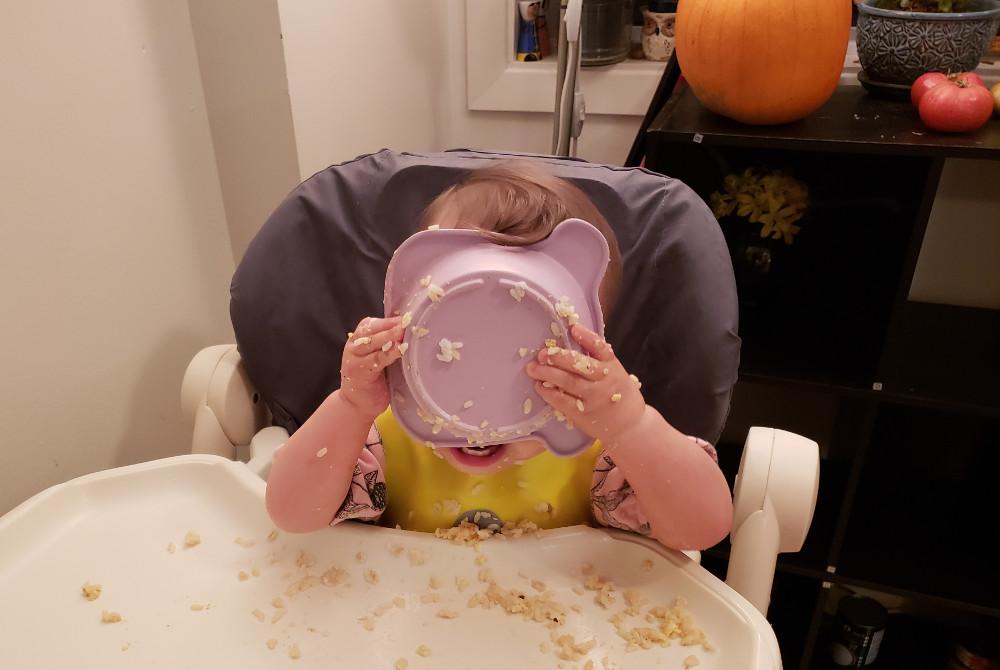 Photo of Toddler Baobao making a very messy stab at self-feeding, November 18, 2020.